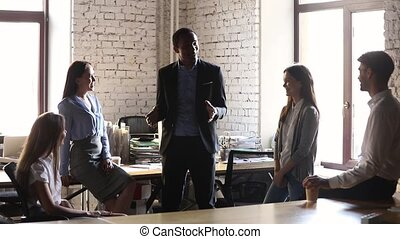 African male leader coach motivating team employees group at...