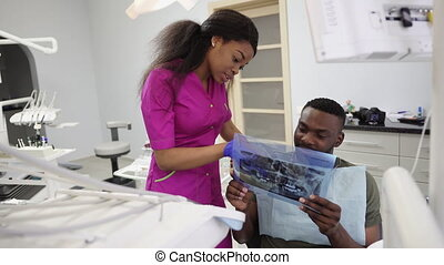 African male patient getting dental treatment in dental clinic. Pretty young African female dentist analyzing x-ray image, teeth photograph and explaining results to patient, man looking attentively