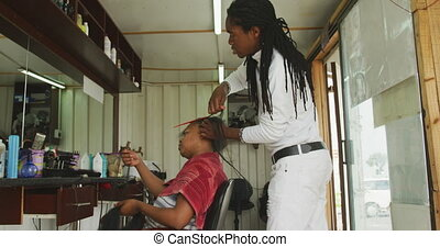 African man adding hair extensions - Side view of an African...
