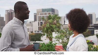 African man and mixed race woman discussing on rooftop