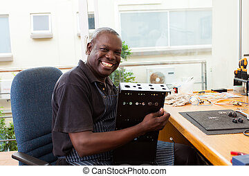 african man assembly electronic equipment