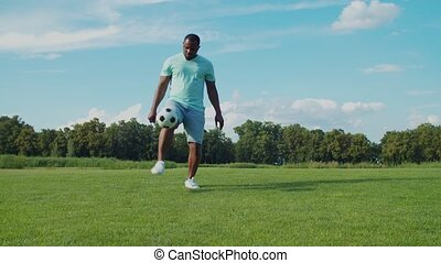 Handsome african man in casual clothes bouncing soccer ball on legs on green grass in public park. Active black guy practicing football, demonstrating skills of controlling and juggling ball in nature