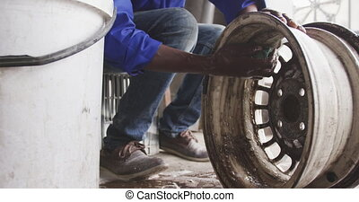 African man cleaning a wheel - Front view of a senior ...