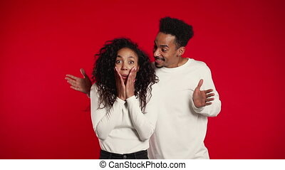 African man closes eyes of his beloved girlfriend before surprise her. Couple in white on red studio background. Love, holiday, happiness concept.