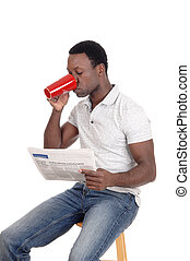 African man drinking coffee, reading the paper