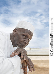 African man, eighty years old - African man sitting in front...