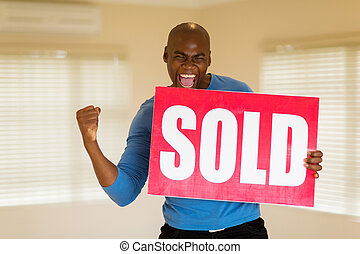 african man holding sold sign in his new house