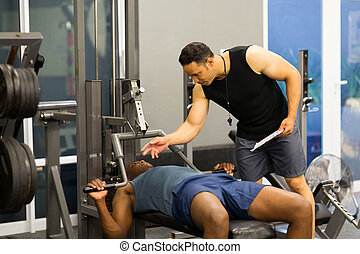 african man in gym with personal fitness trainer