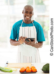 african man in kitchen using tablet computer