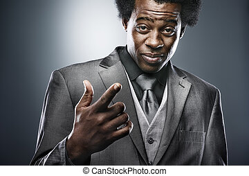 african man in suit gesturing with hand
