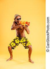 African man in swimwear shooting with water gun - Full...