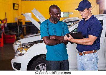 african man inside vehicle workshop with auto mechanic