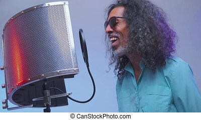 African man is singing in the studio - Bearded man in ...