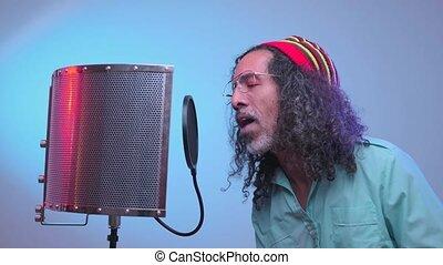 African man is singing in the studio - Emotional rastaman is...