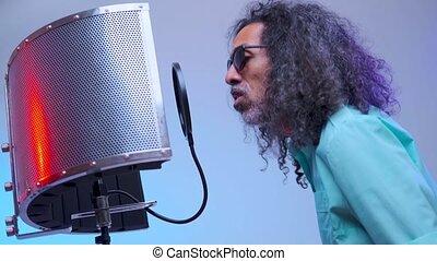 African man is singing in the studio - In the light studio ...