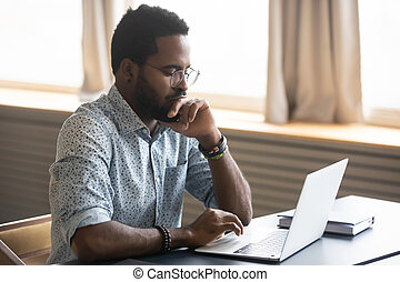 African man looking at laptop screen thinking over received email