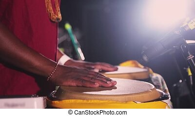 African man play bongo drums on open air night party. Entertainment. Hands fastly beating rhythm. Microphone