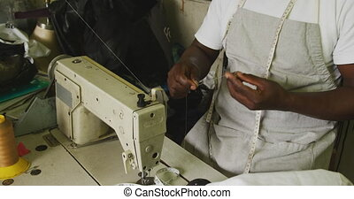 African man preparing the thread for sewing - Front view of ...