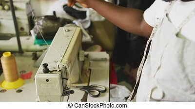African man preparing the thread for sewing - Side view of ...