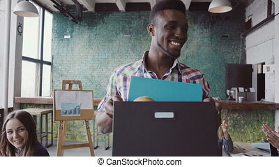 Handsome african man recently hired at start-up company comes into new office. Male holds box with personal belongings, greets with new colleagues, unpacked stuffs at new workplace. Mixed race team.