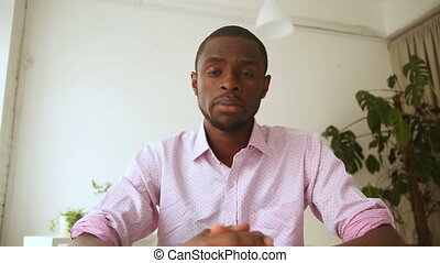 African man recording video message, talking on webcam at...