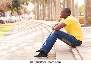 african man relaxing in urban city - side view of african...