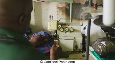 African man sewing tissue - Rear view of an African male ...