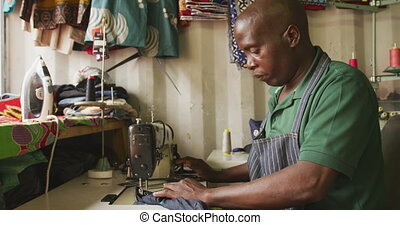 African man sewing tissue - Side view of an African male ...