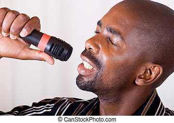 african man singing loudly on a karoake microphone