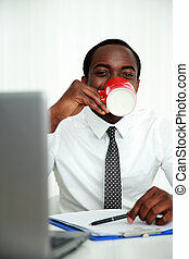 African man sitting at his workplace and drinking coffee in office