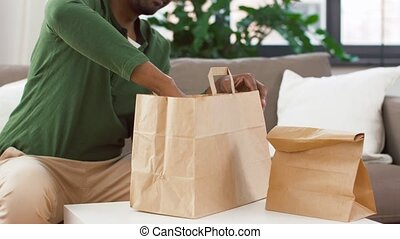 african man unpacking takeaway food at home - consumption, ...