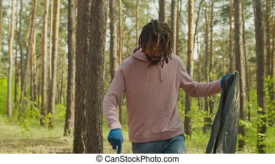 Handsome african man volunteer in casual clothes wearing protective gloves, picking up garbage and plastics using garden tool during cleaning forest, caring and preserving ecology.