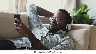 Smiling young adult mixed race african man wear wireless headphones relax on sofa listening mobile music or learning foreign language audio course in smart phone app lying resting on couch at home