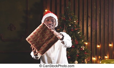African man with a gift in hands on background of Christmas tree.
