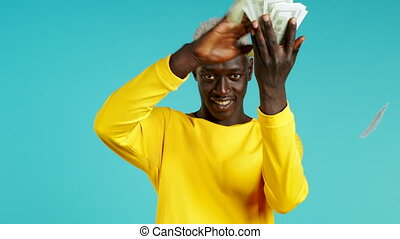 African man with surprised happy face scatters, waste money. Person overspend US. Guy in yellow is flush with dollars on blue studio background. High quality 4k footage