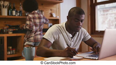 African man working while mixed race woman preparing breakfast