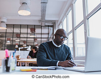 African man writing notes while working on a laptop