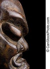 African mask over black background