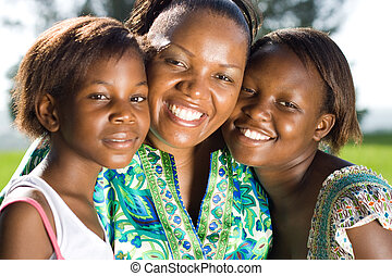 african mom - an african woman with her daughters at the...