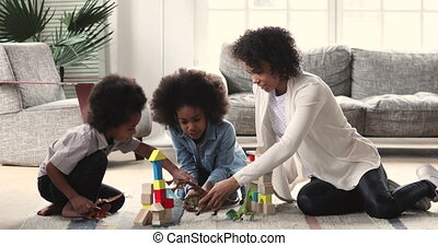 African mom babysitter playing with kids on living room floor