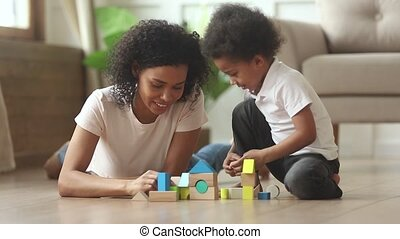 African mom helping kid son building castle from wooden...