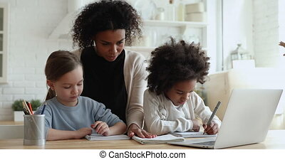 African mom, tutor helping two mixed race girls studying ...