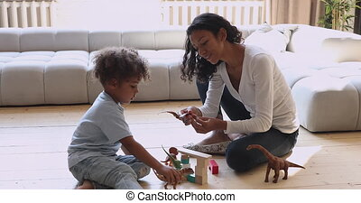 African mom with kid son playing toys sit on floor
