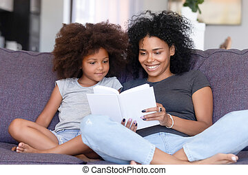 African mother and little daughter sitting on couch reading book