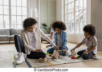 African mother play with kids with wooden bricks at home