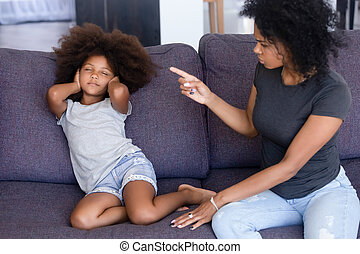 African mother scolding little daughter sitting on couch at home