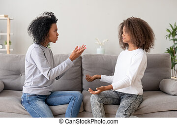 African mother scolding teen daughter sitting on couch at home