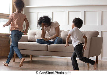 African mother sit on couch can't handle with noisy kids