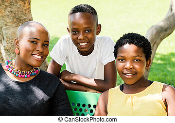 African mother with two kids outdoors. - Close up portrait...
