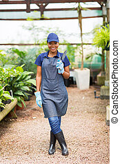 african nursery owner holding a shovel